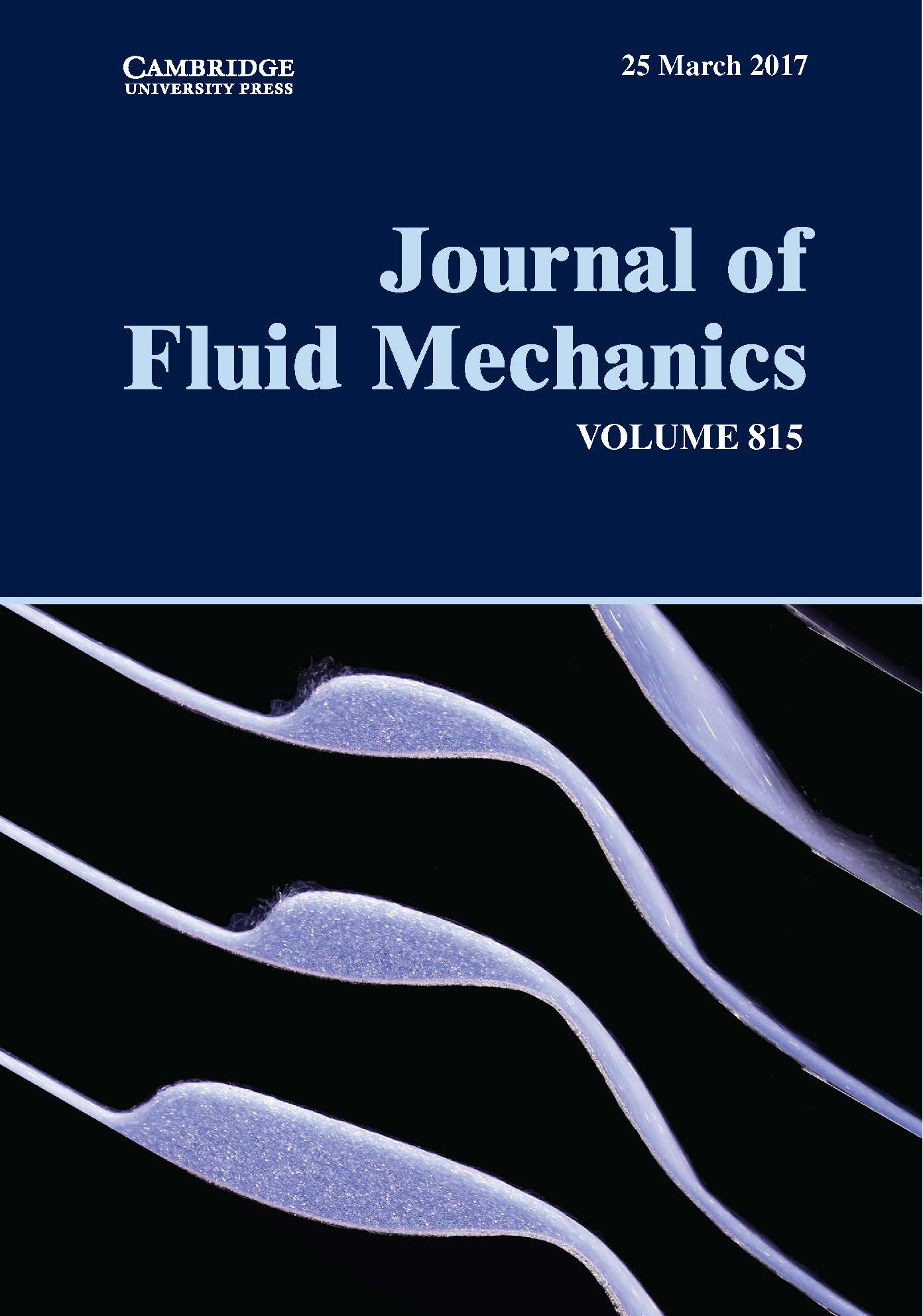 Multiple solutions for granular flow over a smooth two-dimensional bump